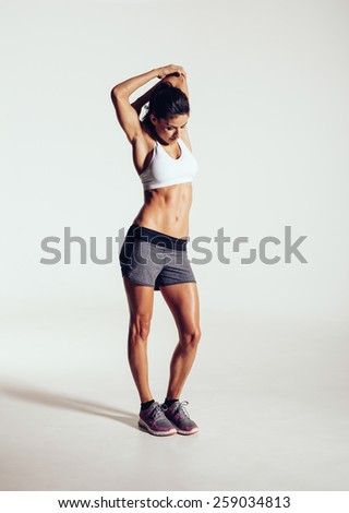 Studio shot of a young woman stretching before exercising. Sporty young woman warming up on grey background. - stock photo