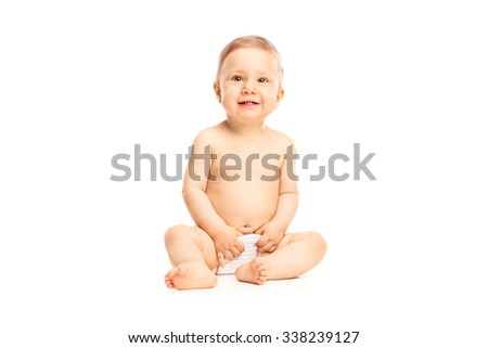 Studio shot of an adorable little baby girl in white diapers smiling and looking up isolated on white background - stock photo