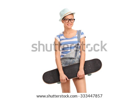 Studio shot of an alternative girl with a turquoise hat holding a skateboard and looking at the camera isolated on white background  - stock photo