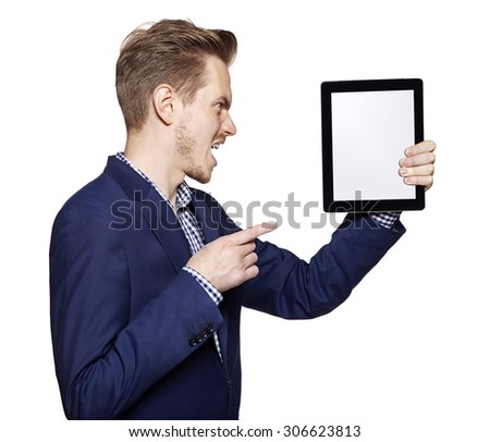 Studio shot of an angry young man shows on a digital tablet. - stock photo