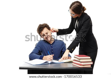 Studio shot of angry teacher twisting the student's ear and pointing him something in his notebook, isolated over white background - stock photo