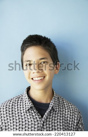 Studio shot of Asian boy smiling - stock photo