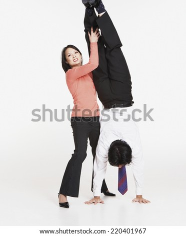 Studio shot of Asian businessman doing handstand with Asian businesswoman's help - stock photo