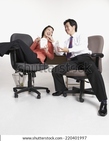 Studio shot of Asian businesspeople eating take out - stock photo