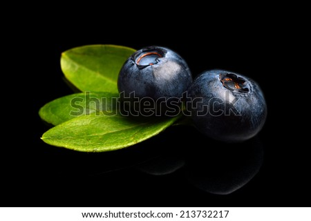 Studio shot of assortment fresh macro close up blueberries with leaves isolated on a black background  - stock photo