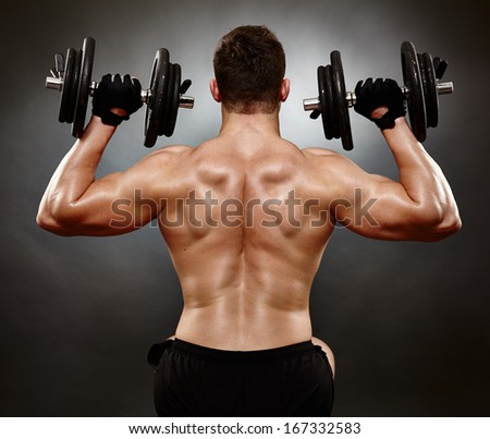 Studio shot of athletic young man working his deltoids with heavy dumbbells - stock photo