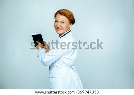 Studio shot of beautiful redheaded female doctor. Medical worker smiling, looking at camera and using tablet computer - stock photo