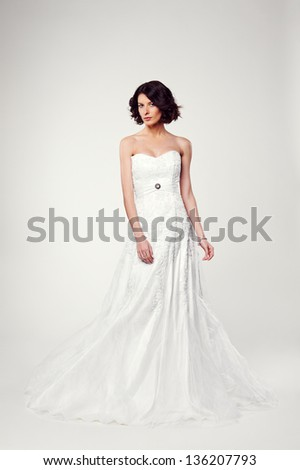 studio shot of beautiful young bride in white long dress - stock photo