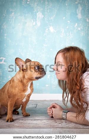 studio shot of beautiful young woman with her pet little dog french bulldog - stock photo