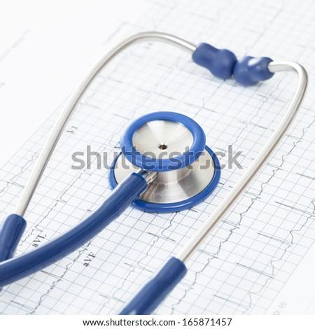 Studio shot of blue stethoscope over ecg graph - stock photo