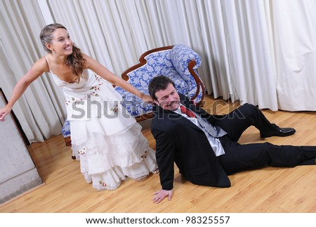 Studio shot of bride and groom. She drags him to the marriage - stock photo
