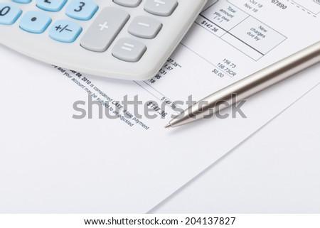 Studio shot of calculator and pen over some receipt - stock photo
