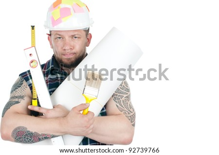 Studio shot of caucasian manual worker with blueprint roll and a heap of different working instruments - stock photo