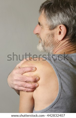 Studio shot of elderly man with shoulder pain - stock photo