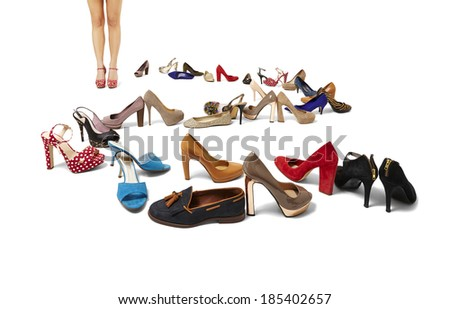 Studio shot of female legs and huge selection of shoes. Copy space.   - stock photo