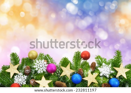 Studio shot of fir branches decorated with stars, snowflakes and cones on a colorful background of out-of-focus glittering lights - stock photo