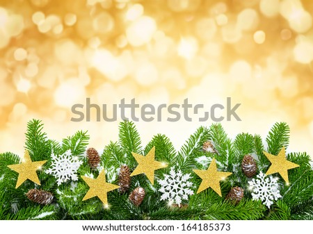 Studio shot of fir twigs decorated with stars, snow and cones on blurred lights background - stock photo