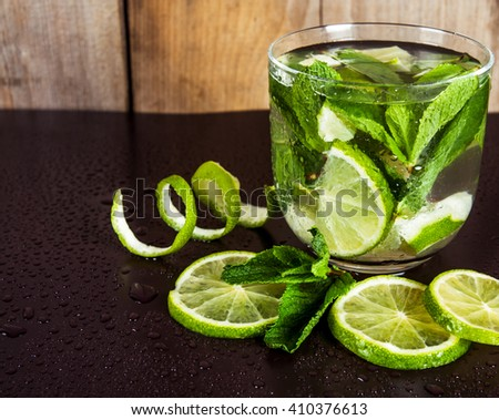 Studio shot of fresh mojito drinks with slime slices, isolated on black background - stock photo