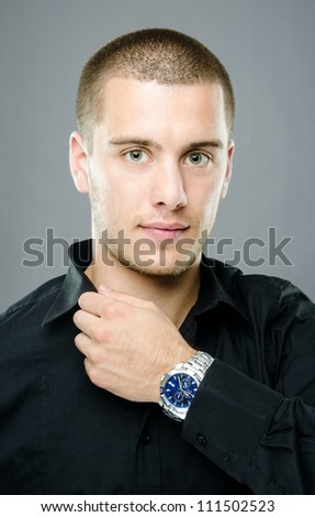 Studio shot of handsome young man with blue luxury watch - stock photo