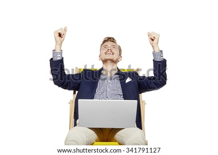 Studio shot of happy young man sitting on sunbed. He raises his arms in a gesture of victory. - stock photo