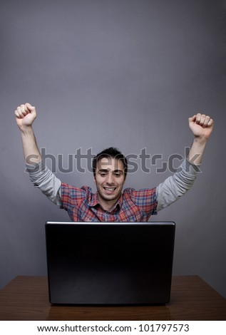 Studio shot of laptop and happy young man with arms raised on gray background with copy space - stock photo