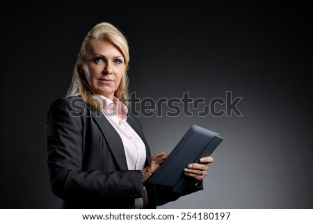 Studio shot of mature businesswoman with a digital tablet  looking at camera against grey background  - stock photo