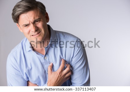 Studio Shot Of Mature Man Suffering Heart Attack - stock photo