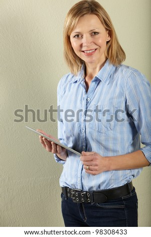 Studio Shot Of Middle Aged Woman Using Tablet Computer - stock photo