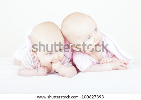 studio-shot of  6 month old identical baby twin sisters lying on bed. - stock photo