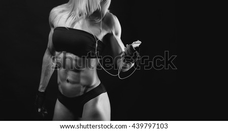 Studio shot of muscular young woman listening music on mobile phone against black background. Attractive blond bodybuilder with a mobile phone. Space for text on the right side - stock photo