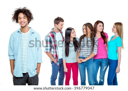 Studio shot of nice young multicultural friends. Beautiful people chatting. Focus on african boy. He looking at camera and smiling. Isolated background - stock photo