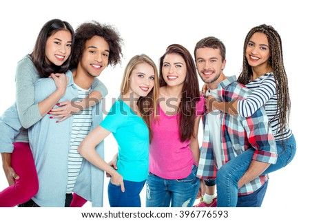 Studio shot of nice young multicultural friends. Beautiful people looking at camera and smiling. Two guys carrying girls piggyback. Isolated background - stock photo