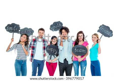 Studio shot of nice young multicultural friends. Beautiful people looking at camera, holding nameplates with different words and smiling. Isolated background - stock photo