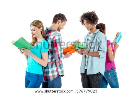 Studio shot of nice young multicultural friends. Beautiful people reading books and smiling. Isolated background - stock photo