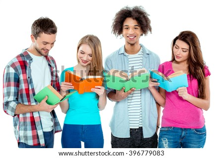 Studio shot of nice young multicultural friends. Beautiful people reading books. One boy looking at camera and smiling. Isolated background - stock photo