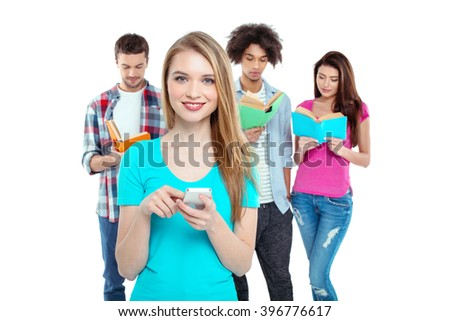 Studio shot of nice young multicultural friends. Beautiful people reading books. One girl using mobile phone, looking at camera and smiling. Isolated background - stock photo