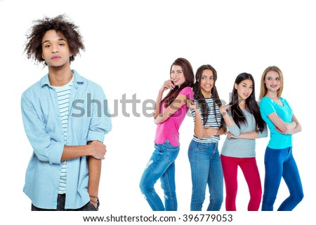 Studio shot of nice young multicultural people. Beautiful girls chatting and looking at young man. Focus on african boy. He looking at camera. Isolated background - stock photo