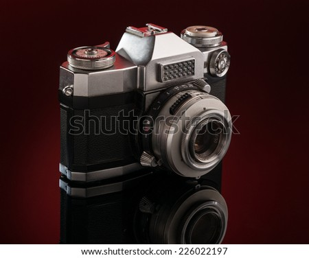 Studio shot of  old-fashioned camera, dark red background - stock photo