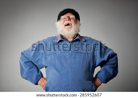 Studio shot of senior man standing with his hands on hips laughing against grey background - stock photo