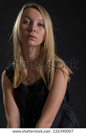 Studio shot of serious blonde woman on dark background - stock photo