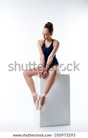 Studio shot of sexy ballet dancer sitting on cube - stock photo