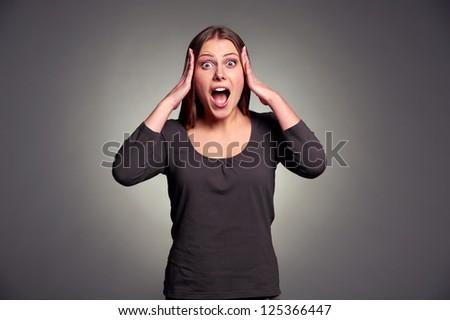 studio shot of shocked young woman over dark background - stock photo