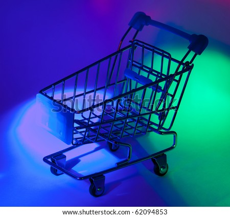 Studio shot of shopping cart in abstract multicolor light. - stock photo