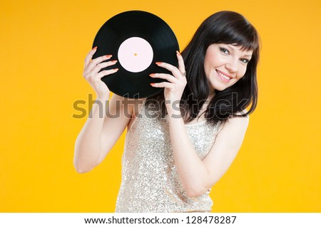 Studio shot of smiling caucasian female with a vinyl record - stock photo