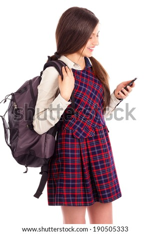 Studio shot of smiling student with backpack looking at  her smart phone over white background - stock photo