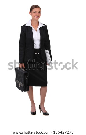 Studio shot of smiling woman in a suit with a briefcase - stock photo
