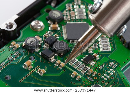 Studio shot of soldering iron and microcircuit - stock photo
