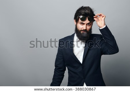 Studio shot of stylish trendy man with beard wearing modern sunglasses and a black suit over a grey background - stock photo