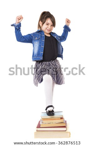 Studio shot of successful girl with one leg on a pile of books isolated on white background - stock photo