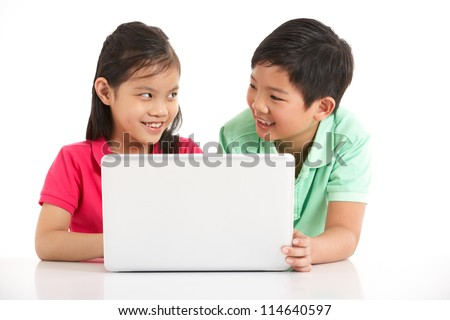 Studio Shot Of Two Chinese Children With Laptop - stock photo